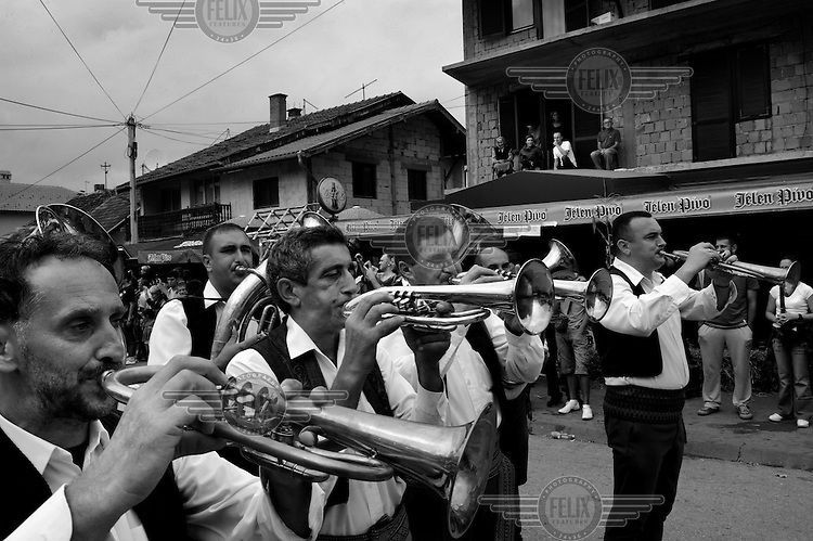 A band parades along a street at the trumpet festival. Hundreds of thousands of visitors gather each year in the small village of Guca for a festival of traditional brass band and folk music, the Dragocevo Trumpet Festival.