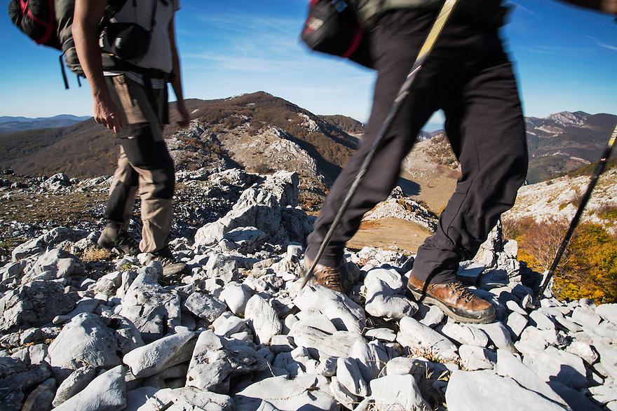 Hikers traversing a limestone ridge in Mehedinti Plateau Geopark, Geoparcul Platoul Mehedinți, Romania.