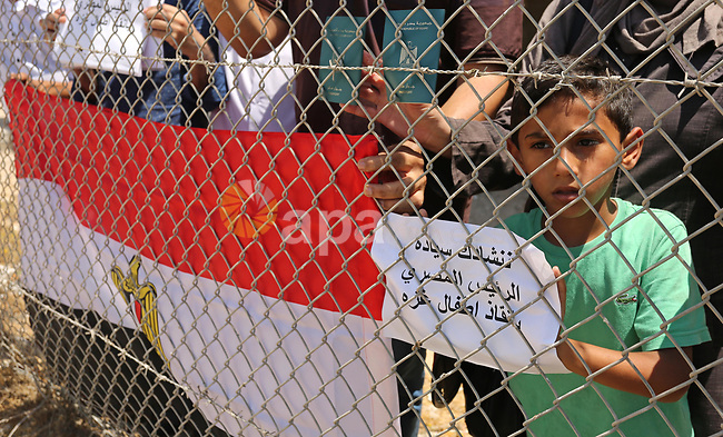 Palestinians gather in front of the gate of Rafah border crossing between Egypt and Gaza during a protest against the blockade calling for reopening of the crossing, in the southern Gaza Strip July 3, 2017. Photo by Ashraf Amra