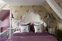 The double bed in this loft bedroom has an ornate silver painted headboard and matching bedside tables.