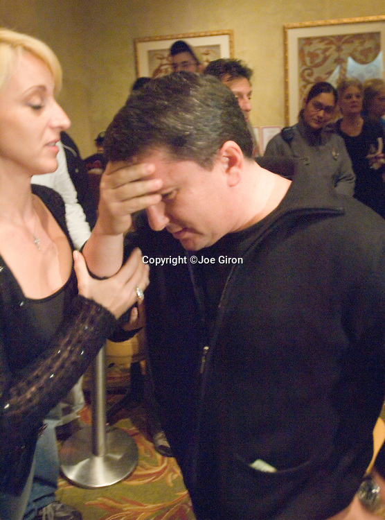 Arthur Azan reacts to being knocked out.  At left is his wife.