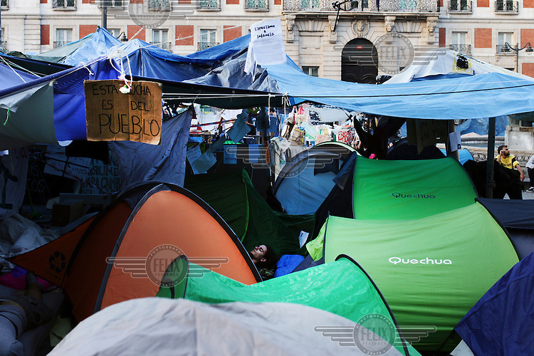 People sleep among tents pitched by the self-named 'indignados' who are protesting against cuts, austerity and joblessness. In May 2012, following a worsening financial crisis and a deepening recession in Spain, thousands of people started to gather in Spanish cities to protest against austerity, the global financial system, high unemplyment rate (Spain's is the highest rate in Europe) and the lack of opportunities. The protest movement has become known as 'los indignados' (the indignant ones).