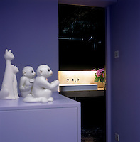 A collection of china animals perch next to the black bathroom which has a pair of oversize shallow basins