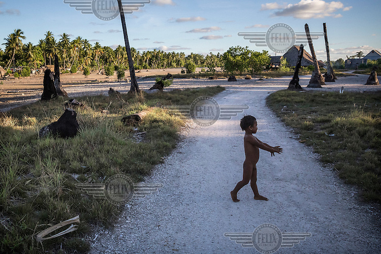 A child crossing a road in Tebunginako village, an area that usually gets flooded during high tide events. The country's government says Tebunginako is a 'barometer for what Kiribati can expect in the future'. Since the 1970s the village's residents have seen the sea levels rise. Eventually the erosion was so great that a major part of the village had to be abandoned.