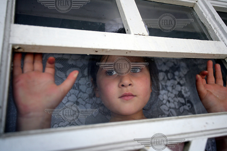 Nine year old Tatiana looking out of the window. She is one of 10 children cared for by an elderly couple in their own home. All the children have either been orphaned or abandoned by their parents.