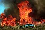 "(05-8-02) SAN BERNARDINO--METRO--A fire fighter near the SUV uses a flare to set backfires to use up what fire officials term, ""fuel"" in order to prevent the recurence of flareups, behind Cal State San Bernardino, Wednesday. STAFF PHOTO BY Rodrigo Peña."