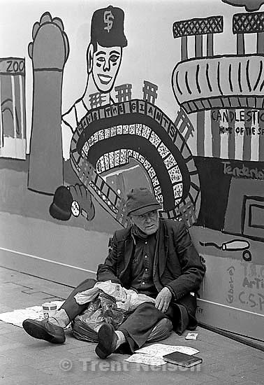 Homeless man under mural<br />
