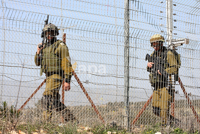 Israeli soldiers stand guards a protest against Israel's controversial separation barrier in the village of Bilin, near the West Bank city of Ramallah, in the Israeli occupied West Bank, on March 4, 2011.photo by Issam Rimawi