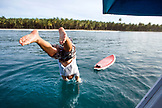 INDONESIA, Mentawai Islands, Kandui Surf Resort, surfer jumping into the Indian Ocean