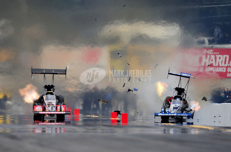Oct. 1, 2011; Mohnton, PA, USA: NHRA top fuel dragster driver Brandon Bernstein (right) blows a tire alongside Doug Kalitta during qualifying for the Auto Plus Nationals at Maple Grove Raceway. Mandatory Credit: Mark J. Rebilas-