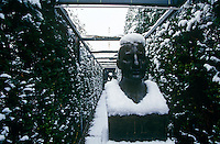 A bust in classical style at one end of the yew pergola in the garden of a house designed by Oswald Mathias Ungers photographed on a snowy day in winter