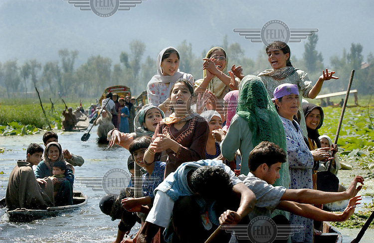 Supporters of Jammu and Kashmir National Conference president Omar Abdullah sing at a rally for him on Dal Lake in the capital Srinagar of Indian Kashmir Sept. 22, 2002.