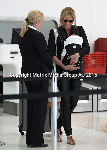16 MARCH 2015 SYDNEY AUSTRALIA<br /> <br /> EXCLUSIVE PICTURES<br /> <br /> Sonia Kruger pictured with her baby daughter Maggie at Sydney Airport checking in for a flight. Sonia was looking taunt and terrific in black leather pants and sandals with Maggie seen for the first time in public on mums chest in a carry harness.