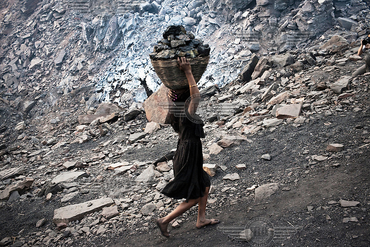 A child carrying out coal from an open cast mine near Bokapahari village. Coal fires rage just below the surface of the ground, making it too hot to walk with naked feet. Noxious gases spew up from fissures, rendering the environment toxic. Residents who live above the furnace make $2 a day collecting small chunks of coal that they sell to illegal middlemen. One or two houses collapse annually into vast underground caverns left unfilled by abandoned mining operations.
