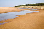 Stream of water flowing across part of Holkham beach, north Norfolk coast, England