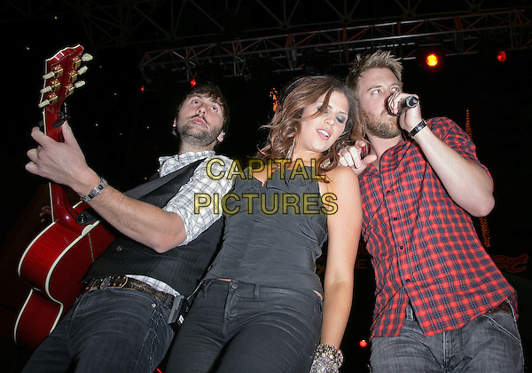 LADY ANTEBELLUM - Dave Haywood, Hillary Scott, Charles Kelley.Lady Antebellum Performs at ACM Weekend at the Freemont Street Experience, Las Vegas, Nevada, USA,16th April 2010..half length music concert gig live on stage country band group microphone singing red checked check black plaid shirt jeans playing guitar waistcoat  strapless bustier top .CAP/ADM/MJT.© MJT/AdMedia/Capital Pictures.
