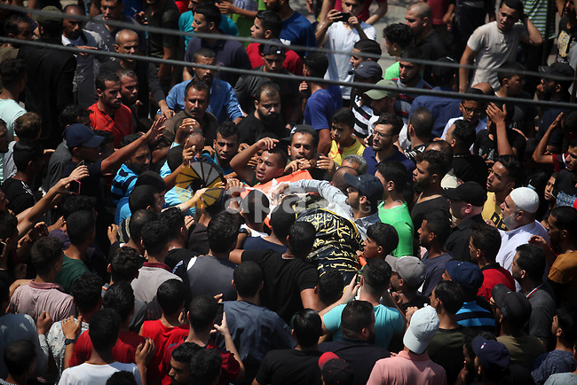 Mourners carry the body of Palestinian Mahmoud Al-walayda, one of three armed Palestinians killed overnight in Israeli fire along the border with the Gaza Strip, mourn during his funeral in Beit Lahya in northern Gaza strip on August 18, 2019. Israeli forces last night killed three Palestinians and injured a fourth one in an artillery attack near the town of Beit Lahia, north of the Gaza Strip, according to the Ministry of Health. Photo by Mahmoud Ajjour