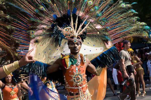 Participants in the West Indian Day Parade dance through the streets in costumes made of feathers.