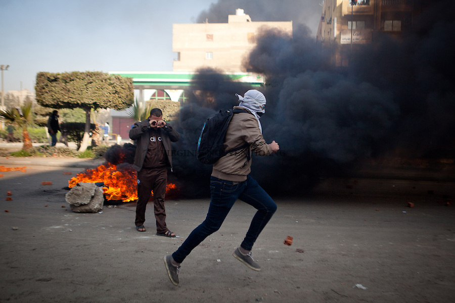 EGYPT, Cairo : Pro Morsi protesters put tires on fire to avoid the smell of tear gas that security forces used to disperse them in Nasr City, January 8, 2014 Toppled by the military in July, Morsi is charged with inciting the killings of opposition activists in clashes outside the presidential palace in December 2012. VIRGINIE NGUYEN HOANG