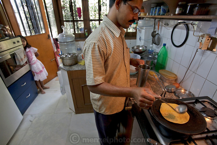 Pulin Sasmal, a cook for Millie Mitra's family in Bangalore, India, prepares a meal while his daughter watches. (From the book What I Eat: Around the World in 80 Diets.)  MODEL RELEASED.