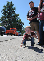 NWA Democrat-Gazette/FLIP PUTTHOFF <br /> CENTERTON DAY PARADE<br /> Braxton Strode, 2, of Rogers picks up candy tossed from parade vehicles while watching the Centerton Day Parade on Saturday Sept. 12 2015 with his dad, Jacob Strode and mom Jaylene Strode. Centerton Day featured the parade, tiny tot pageant, live music, auction and a fishing derby.