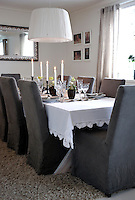 The dining chairs are covered in soft, grey loose covers which complement the natural tones of the rest of the dining area