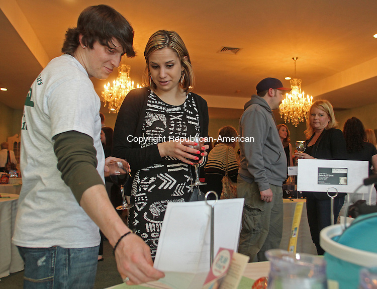 Winsted, CT-041914MK31  Tim Mcgrane and Lydia Micca look look at items on silent auction during the Pleasant Valley Drive-in fund raiser at Crystal Peak in Winsted on Saturday evening.  Donna McGrane  said that over 200 tickets had been sold for the event. The theater needs to raise up to $100,000 in order to open for the 68th consecutive season. More than 60 items were auctioned to raise funds to secure a new digital projector. Last year, the McGranes participated in a contest sponsored by Honda that gave away nine digital movie projectors around the country to save drive-ins that might otherwise have closed. Many drive-ins faced the prospect of closing because movie distributors shifted from 35-mm film to an all-digital format at the end of last year. The digital projectors cost about $80,000 and many drive-ins cannot afford the cost. Michael Kabelka / Republican-American