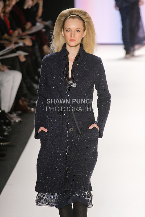 Daria Strokous walks runway in a deep navy embroidered cowl neck dress, indigo melange knit coat from the Carolina Herrera Fall 2012 collection, during Mercedes-Benz Fashion Week Fall 2012 in New York.