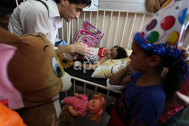A Palestinian dressed as a clown tries to cheer up an injured Palestinian child, at the Shifa hospital in Gaza city, on August 10, 2014. where he is receiving treatment for Injuries caused by Israeli shelling on neighborhoods in Gaza City. Photo by Ashraf Amra
