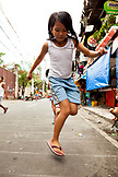 PHILIPPINES, Manila, young girl plays in the street in the Intramros District