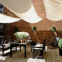 Sail-like awnings provide shade for this decked walled garden