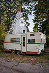 Travel trailer and cement tipee at roadside near Flathead Lake, Montana