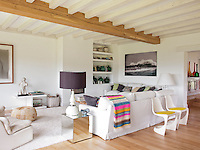 The sitting room has exposed ceiling beams and a wood floor. The neutral decoration creates a fresh and airy feel.