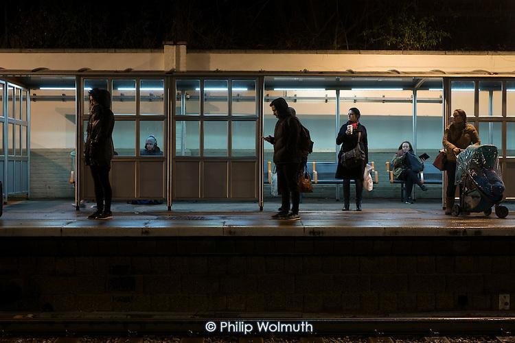Passengers wait on Hampstead Heath London Overground station platform after dark