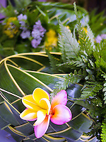 Yellow and pink plumeria and ferns adorn a new woven lauhala basket. Lauhala weaving is an ancient Hawaiian craft and tradition.
