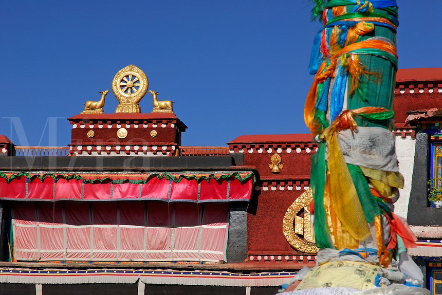 Wheel of Law on Jokhang Temple roof with foreground prayer-flag pole, or darchen, Lhasa, Tibet.
