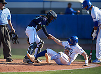 Victory Charter School Knights Lizandro Garcia (21) helps base runner Quinn Blackman (26) up after tagging him out at home during a game against the IMG Academy Ascenders on February 28, 2020 at IMG Academy in Bradenton, Florida.  (Mike Janes/Four Seam Images)