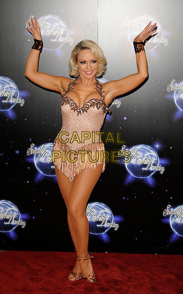 KRISTINA RIHANOFF .At the Strictly Come Dancing Launch Show TV recording, London, England, UK, September 8th 2010..full length  halterneck top costume dress  beige sparkly strappy gold sandals arms raised up cuffs tassels .CAP/CAN.©Can Nguyen/Capital Pictures.