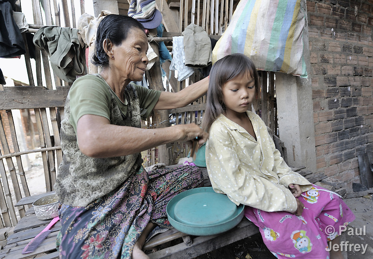 A woman combs her daughter's hair in the Chamroen neighborhood of Phnom Penh, Cambodia.