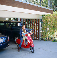Elizabeth Netto with one of her daughers pictured on a scooter in front of the large garage which has room for two cars