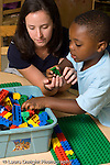 Preschool 4-5 year olds female student teacher working with boy in classroom vertical