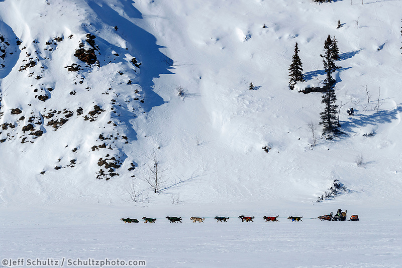 Jeff King sits down on his sled as his team runs next to cliffs on the trail between the Manley and Tanana checkpoings during the 2017 Iditarod on Tuesday March 7, 2017.<br /> <br /> Photo by Jeff Schultz/SchultzPhoto.com  (C) 2017  ALL RIGHTS RESVERVED