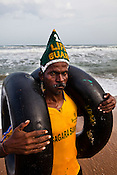39 year old lifeguard, Udapi Krishna Rao poses with two rubber tubes on Puri Beach along the Bay of Bengal in Puri, Orissa, India. A dip in its salty waters is believed to hold great religious significance, as a result these golden sand beaches sees is a never-ending rush of pilgrims and tourists. Photo: Sanjit Das/Panos