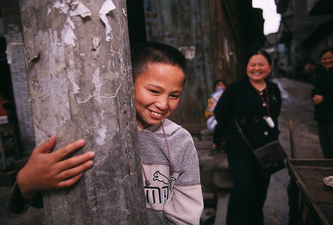 Smiling young boy on street corner; mother; in old Fengdu to be razed for 3 Gorges Dam project; China, Asia; 041803