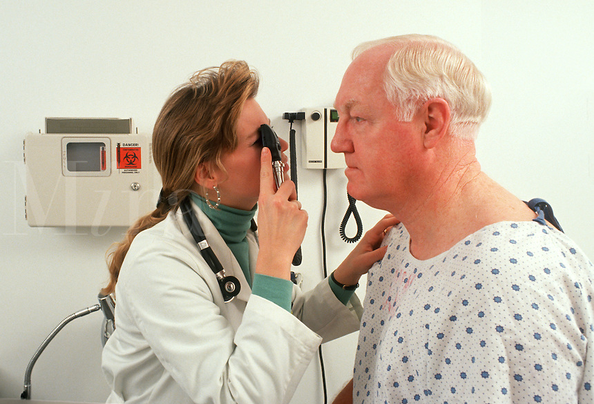 A physician checks the eyes of a mature patient during an office visit.
