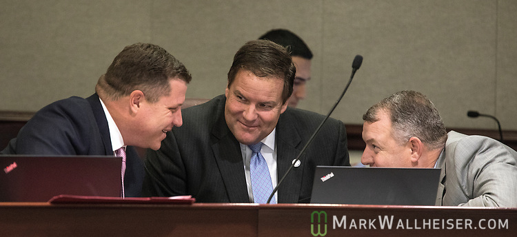 From left, Senators Jeff Brandes (R-St Petersburg), Aaron Bean (R-Jacksonville) and Rob Bradley (R-Orange Park) talk during the Florida Senate Committee on Criminal Justice meeting at the Florida Capitol in Tallahassee Florida March 13, 2017.
