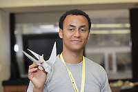 New York, NY, USA - June 23, 2012: Sipho Mabona, from Switzerland, holds one of his original designs, a complex Origami model of a swallow at a class he is teaching during the OrigamiUSA 2012 convention held at Fashion Institute of Technology in New York City. This model is folded from one square sheet of paper.
