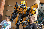 Two boys pose with a Transformers figure in front of Transformers The Ride at Universal Studios Hollywood, Los Angeles, CA, USA