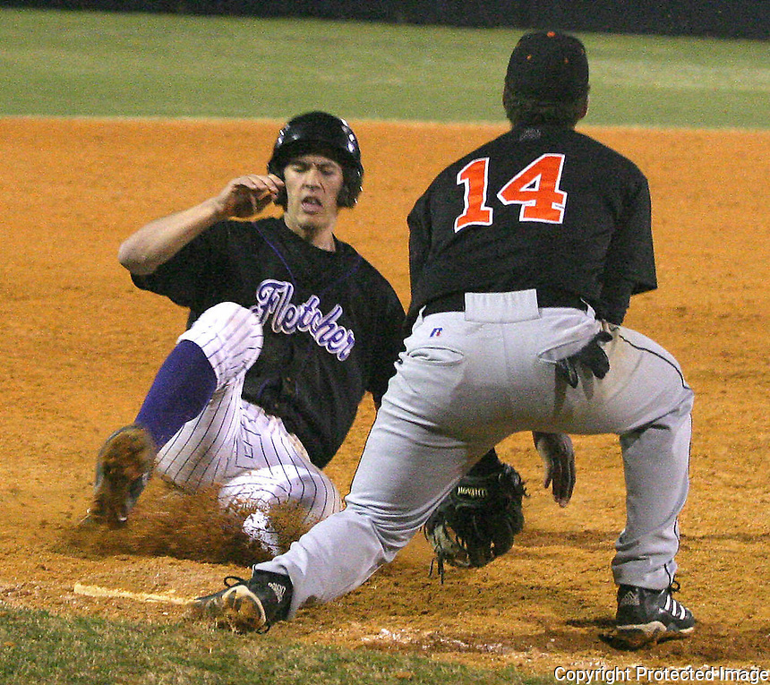 03/02/06....Gary Wilcox/The Times Union....Fletcher High School baseball player   Sam Perry (#9) slides into first base at the Orange Park  at  Fletcher Baseball game  last Month (02/28/06).