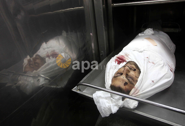 The body of Palestinian Hamas militant Louai Abu Jarad is seen at the morgue of a hospital in Beit Lahia, northern Gaza Strip, on October 24, 2012. Palestinians fired more than 40 rockets from the Gaza Strip into Israel injuring three people, while Israeli air strikes on the territory killed three militants, police and medics said. Photo by Ashraf Amra